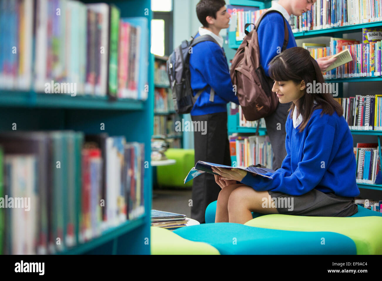 Students reading books in library - Stock Image