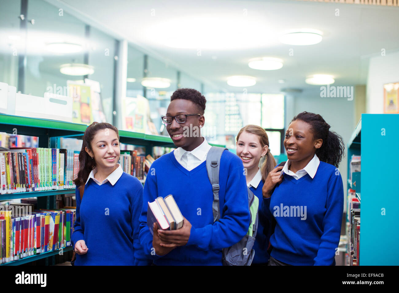 Cheerful students wearing blue school uniforms walking through library - Stock Image
