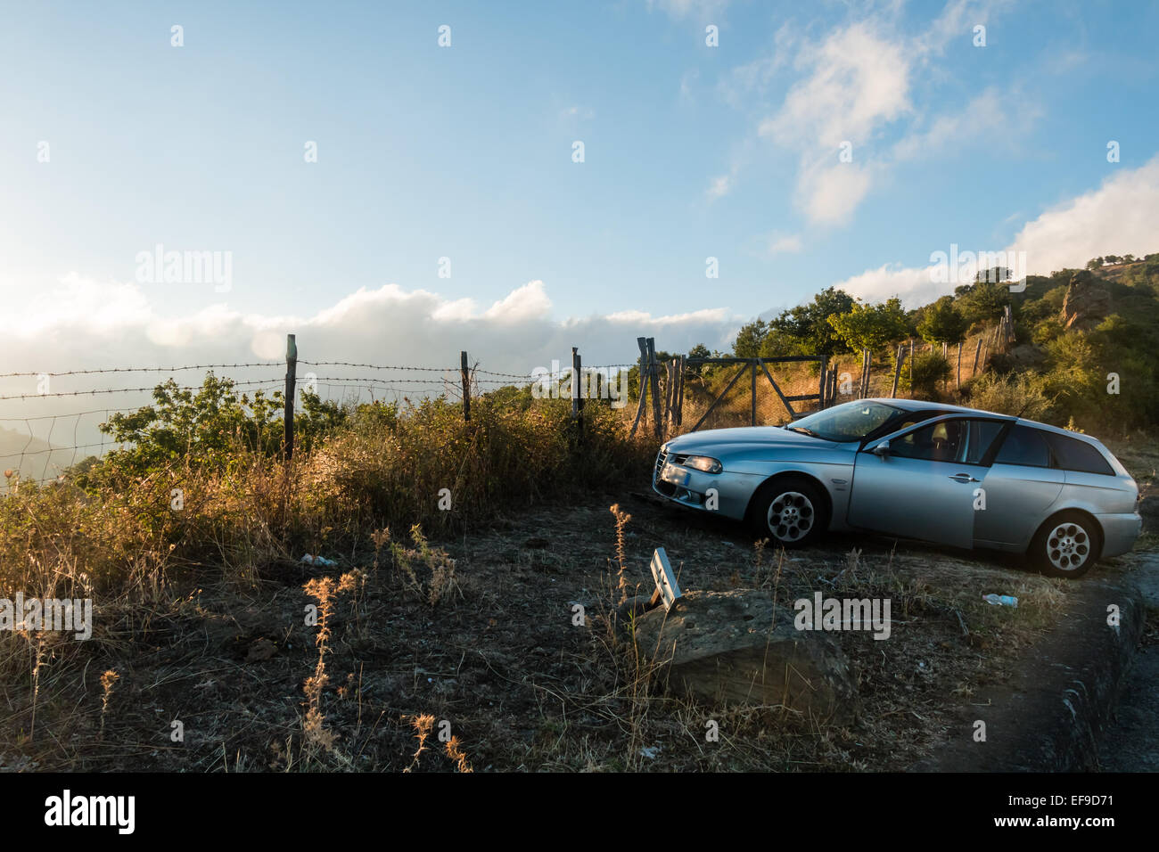 Abandoned car in the corner of the street - Stock Image