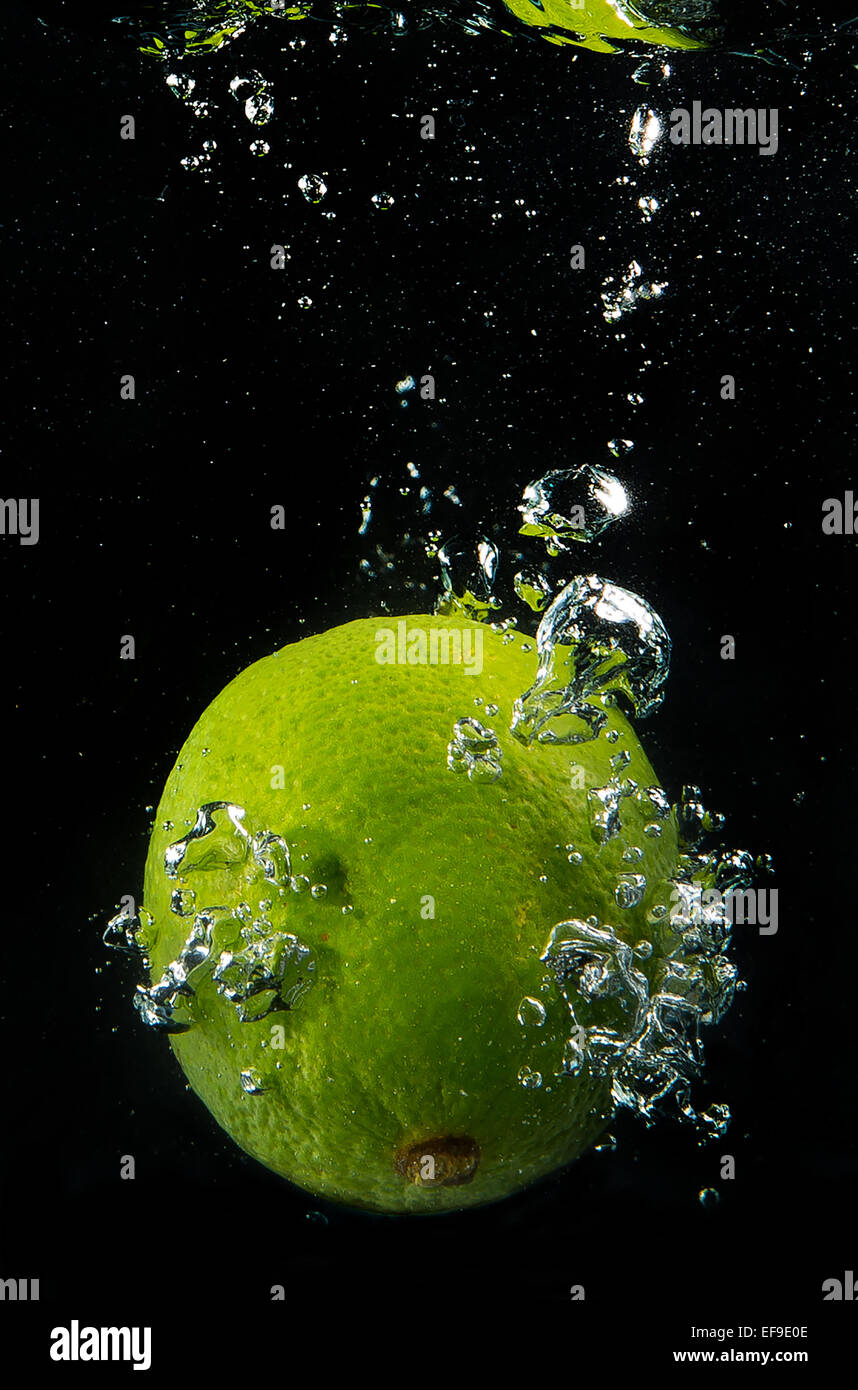 a lime submerged in water - Stock Image