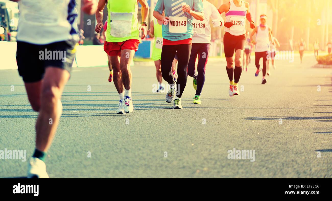 marathon runners runnning on city road - Stock Image