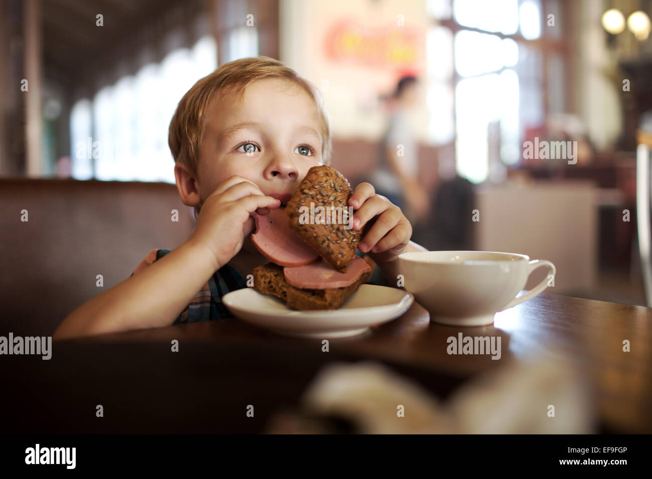 Little child having lunch with sandwich and tea in cafe - Stock Image