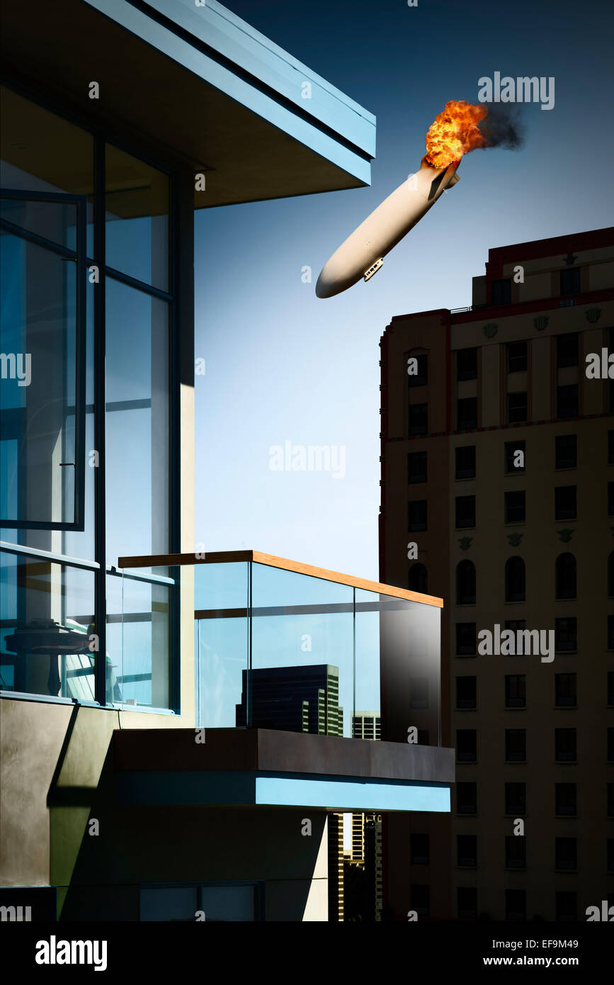 View of city from empty balcony of apartment building with burning blimp in sky - Stock Image