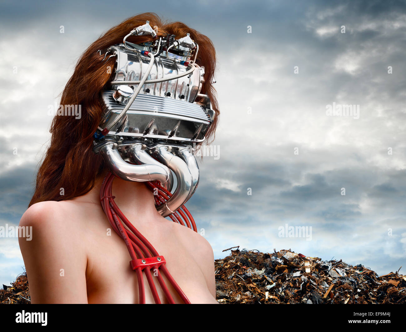 Horizontal fantasy image of woman with a car engine for a head with a junkyard behind her - Stock Image