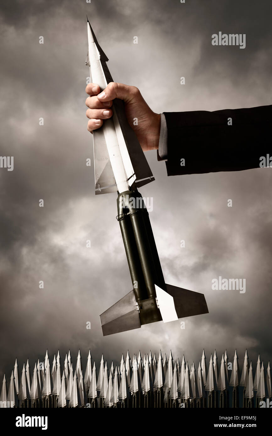 Nuclear missile being grasped by a giant hand against dark stormy sky with a field of many other missiles below - Stock Image