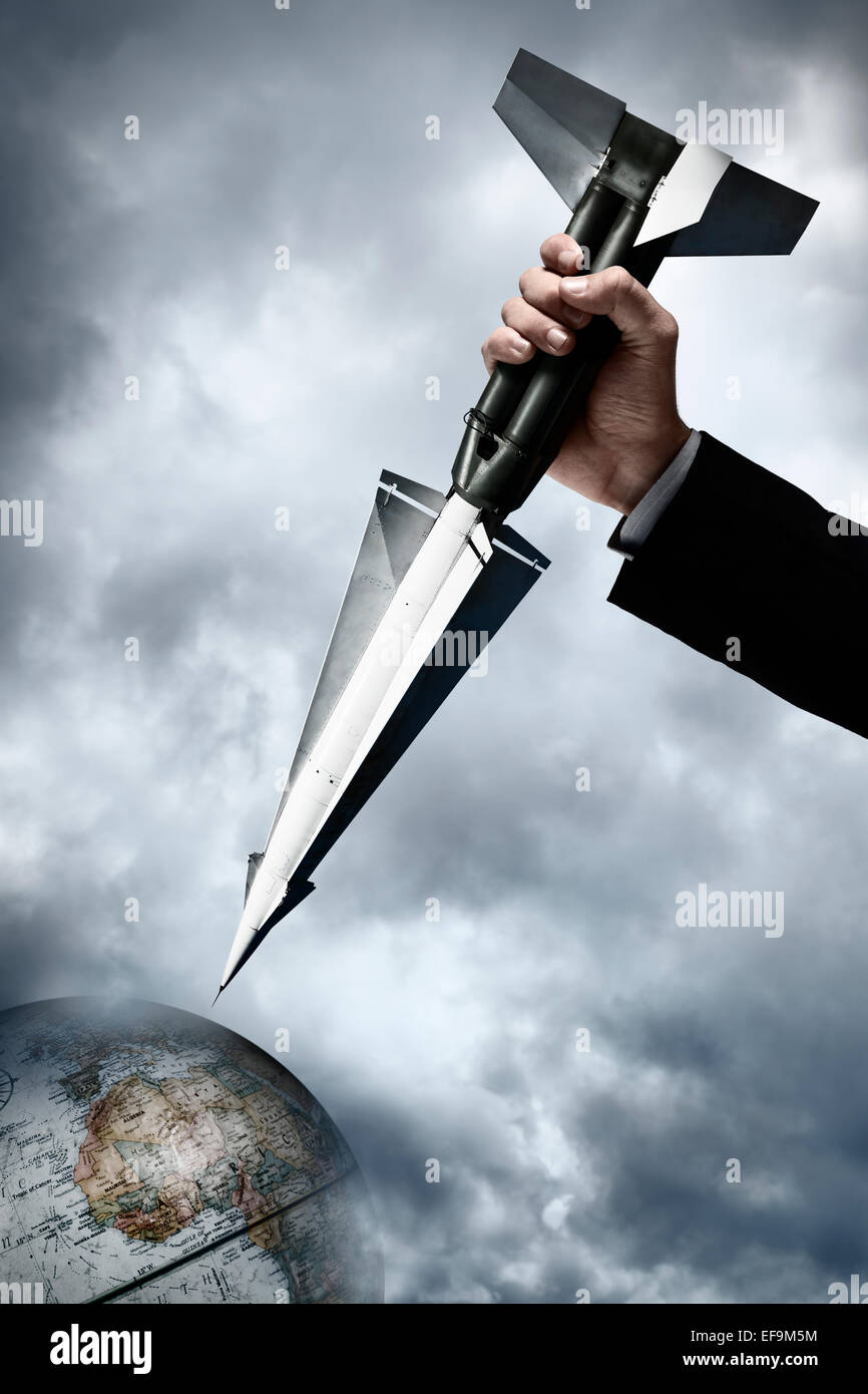Nuclear missile being grasped by a giant hand and pointed down at globe surrounded by a dark stormy sky - Stock Image