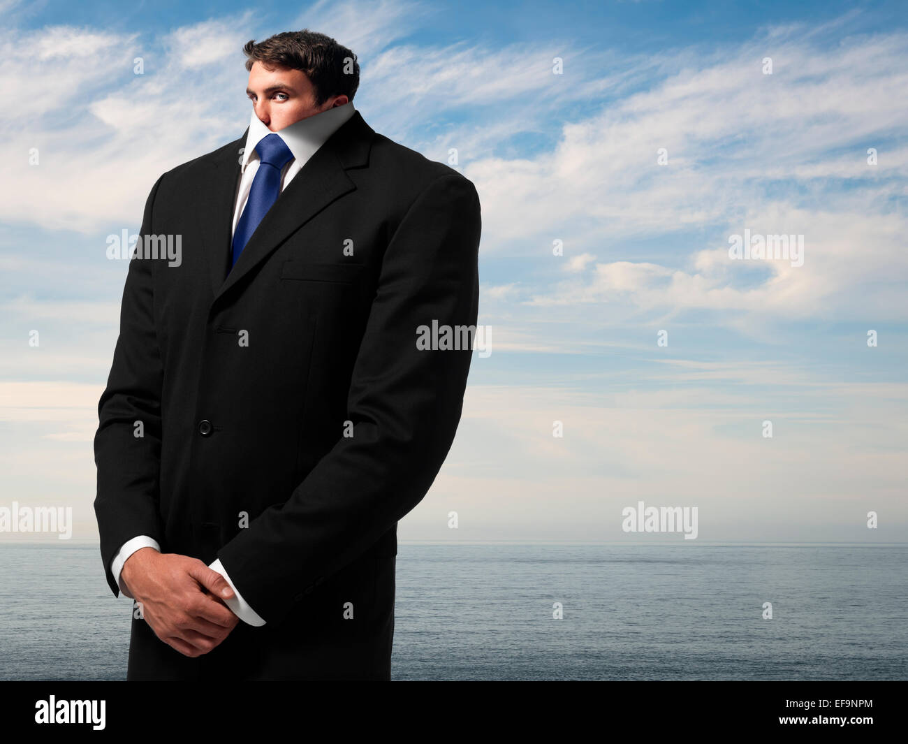 Fantasy image of man in business suit near ocean whose head has shrunk down into his body - Stock Image