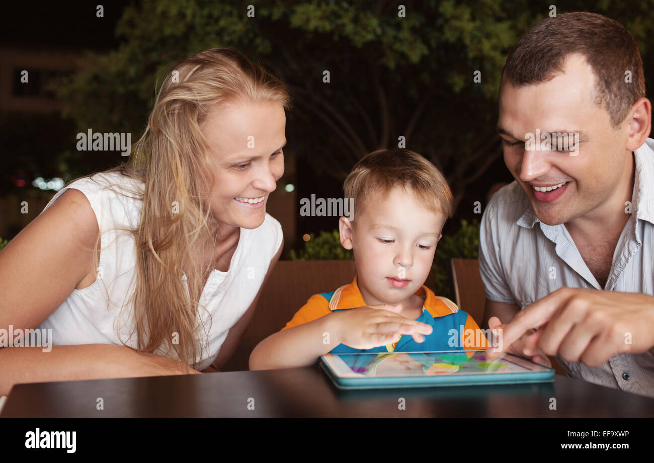 Family of three spending time in cafe with tablet computer - Stock Image