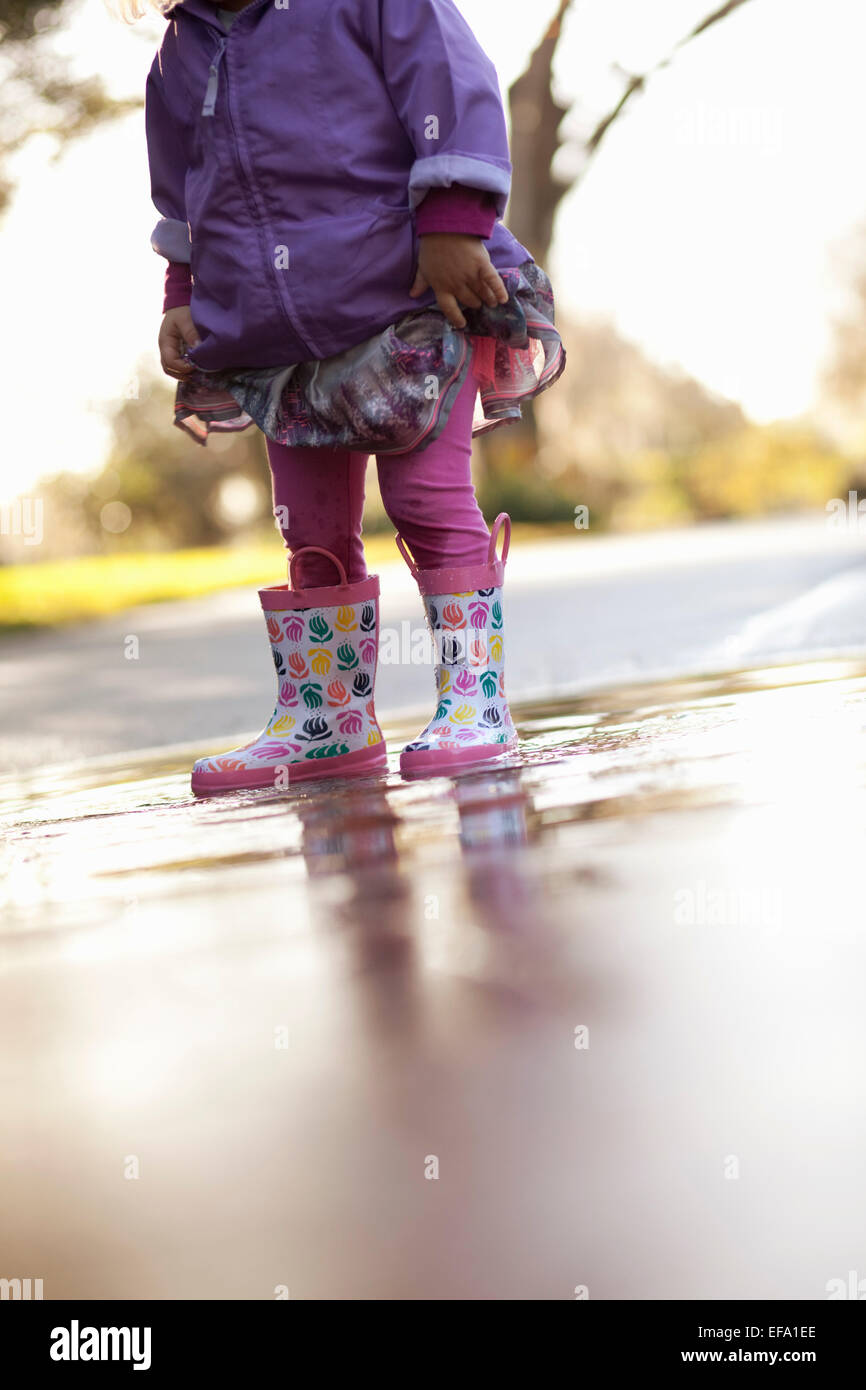 A little girl wearing rain boots stands in a puddle in the street. Stock Photo