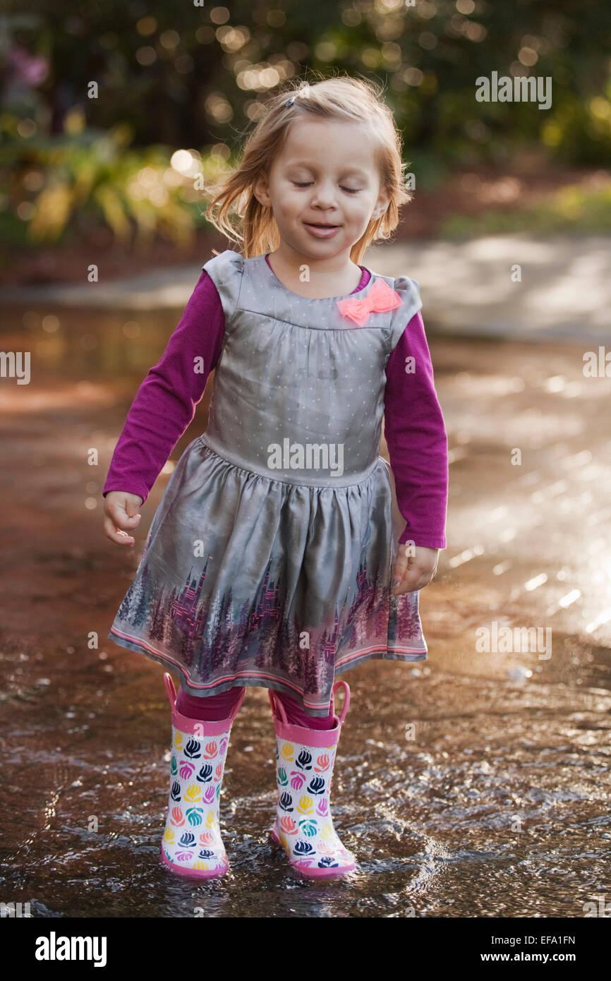 A little girl wearing rain boots
