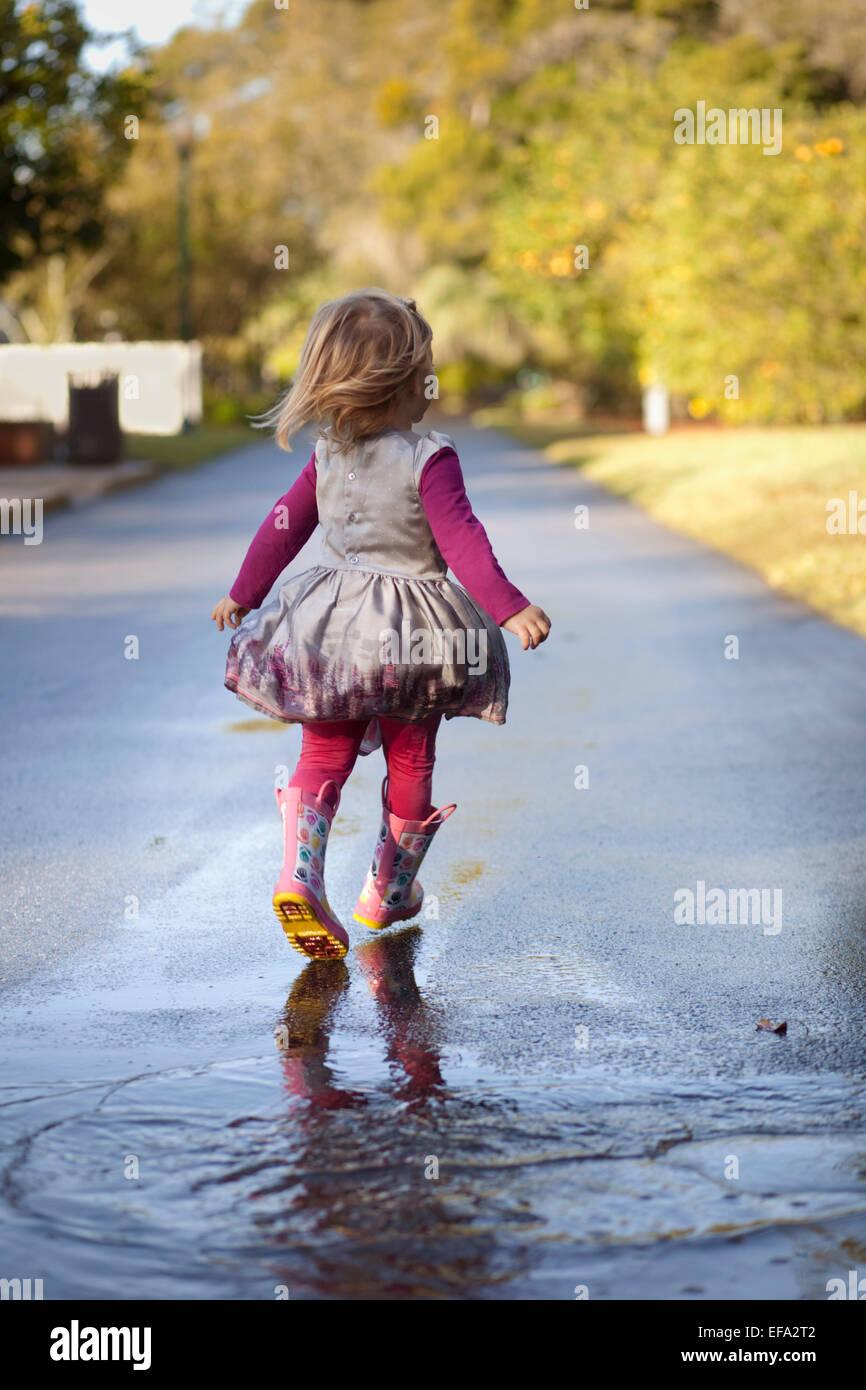 A Little Girl Wearing Rain Boots Runs Through Puddles On A