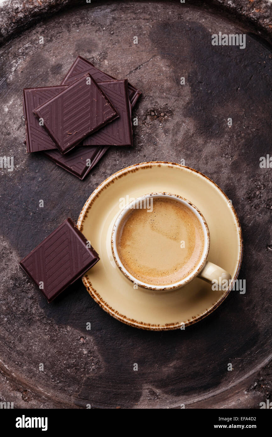 Coffee cup with chocolate on dark textured background - Stock Image