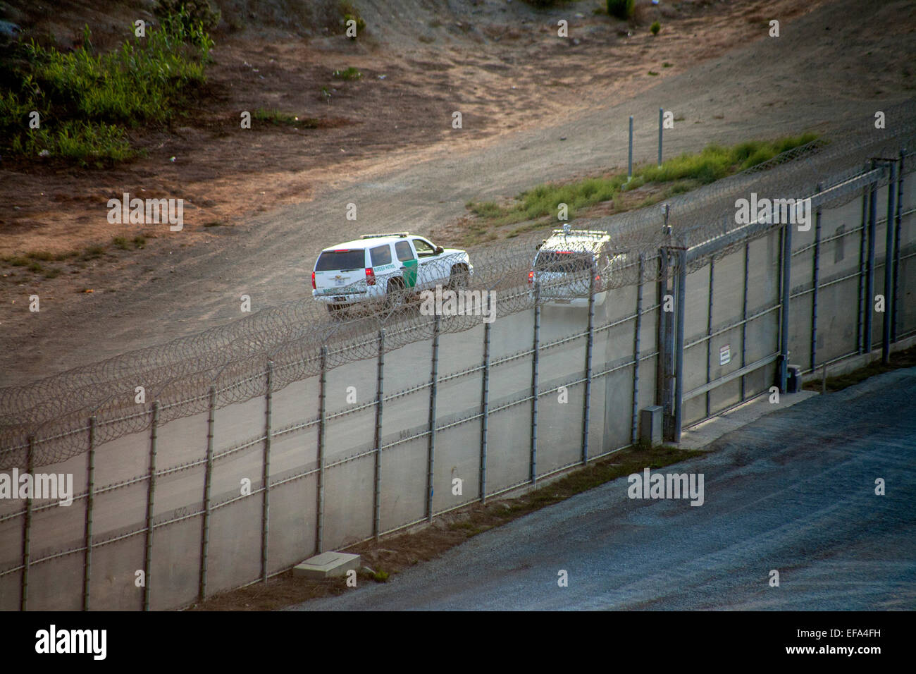 Two Border Patrol SUVs police the U.S./Mexico Border near Tijuana. The Border Patrol is part of the U.S. Department - Stock Image
