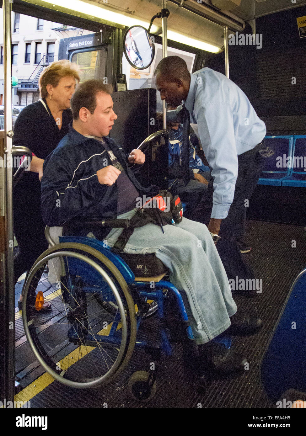 a handicapped passenger in a wheelchair boards a new york city bus