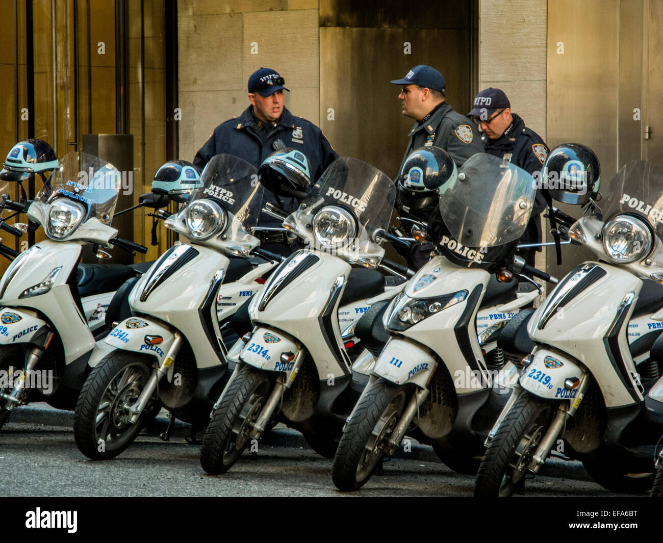 New York City Police Department motor scooters are lined up at a Manhattan sidewalk. Note uniformed officers. - Stock Image