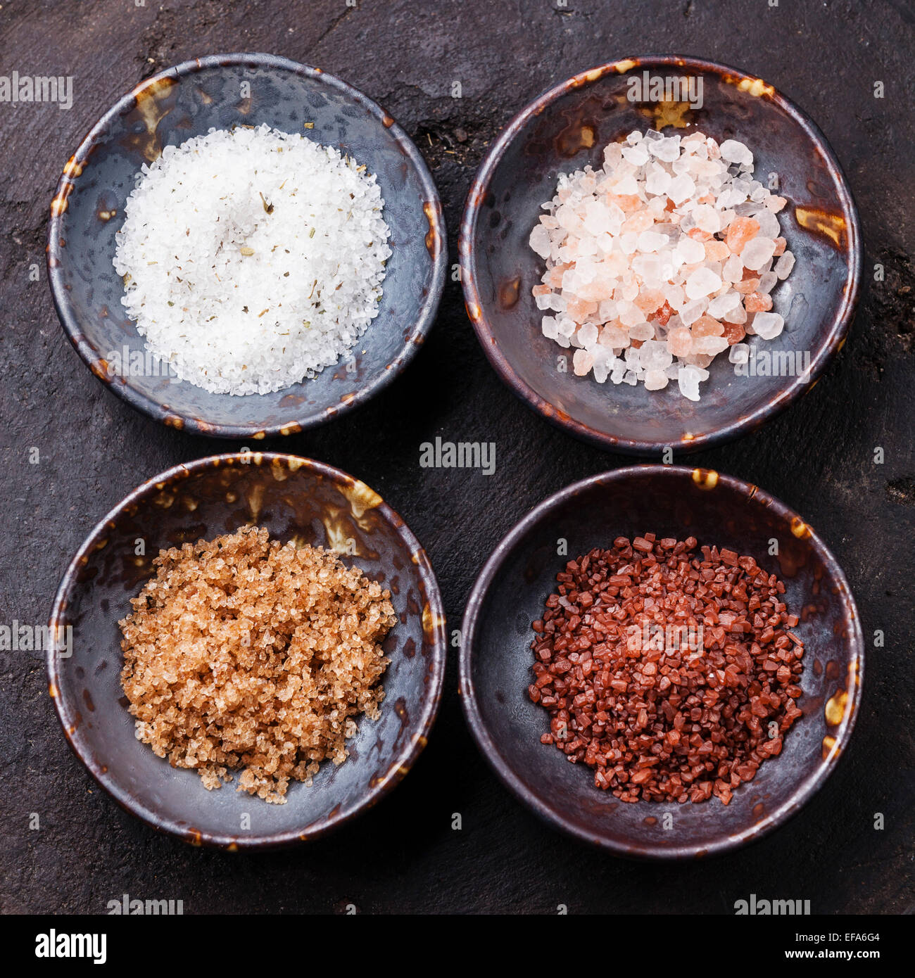 Different types of food coarse Salt in ceramic bowls on dark background - Stock Image
