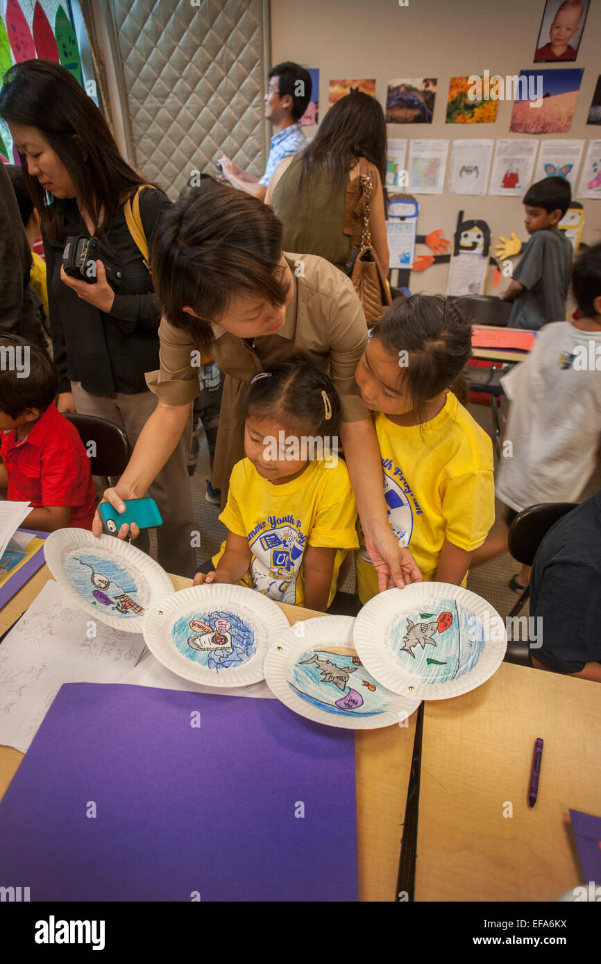 An Asian American mother shows her children student art on paper plates on parents day in an Irvine, CA, elementary - Stock Image