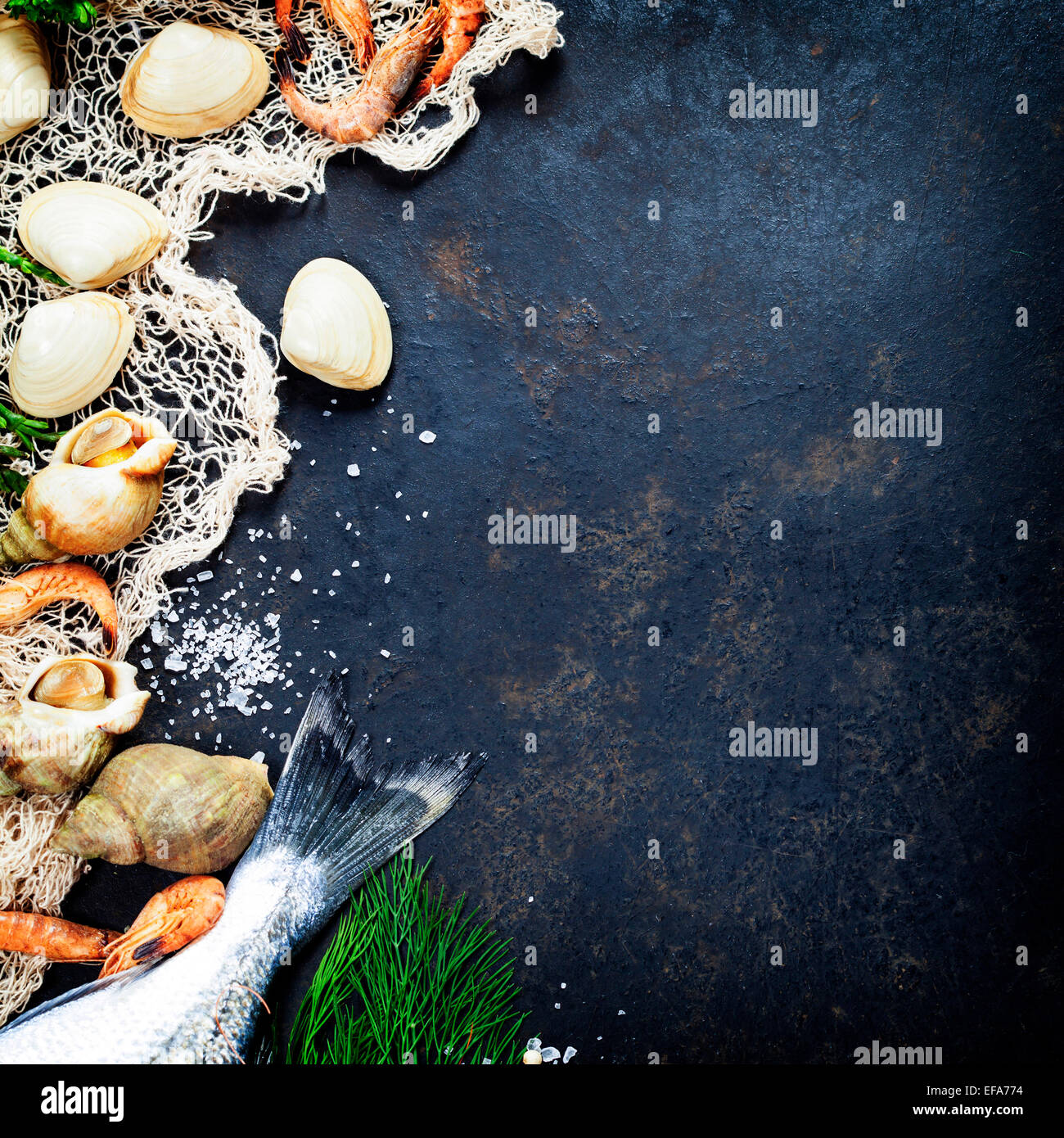 Delicious fresh fish and seafood on dark vintage background. Fish, clams and  shrimps with aromatic herbs, spices - Stock Image