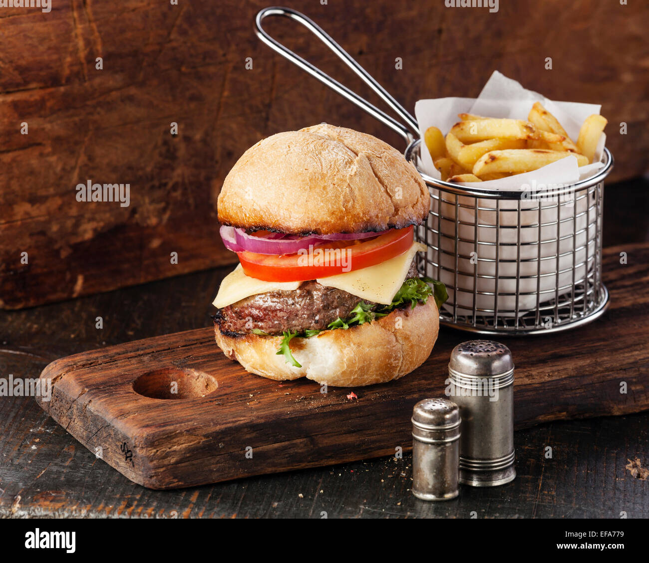 Burger with meat and French fries in basket on wooden background - Stock Image