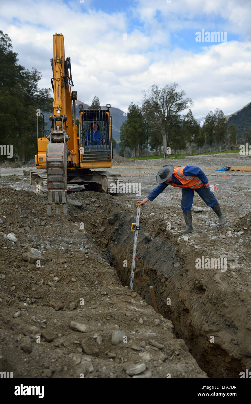 A tradesman checks the depth of a new stormwater drain - Stock Image