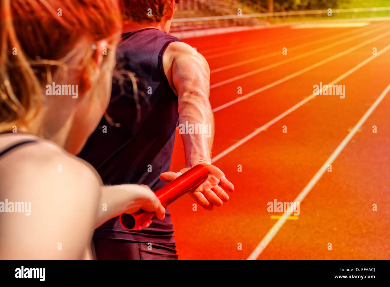 Relay race handing over from woman to man - Stock Image