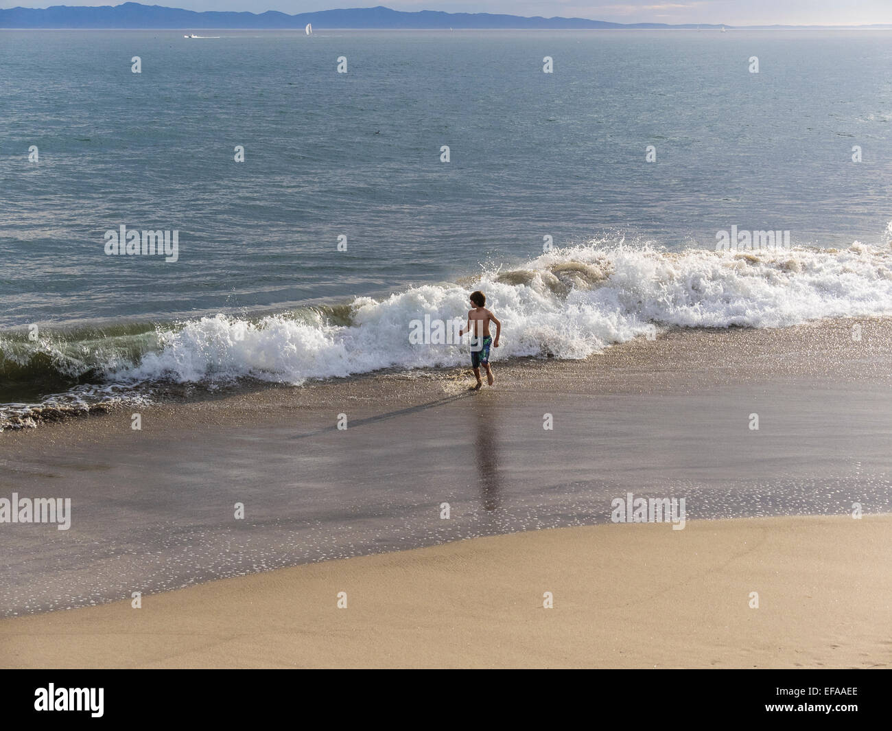 A young boy in a bathing suit plays in the surf at the beach in Santa Barbara, California. - Stock Image