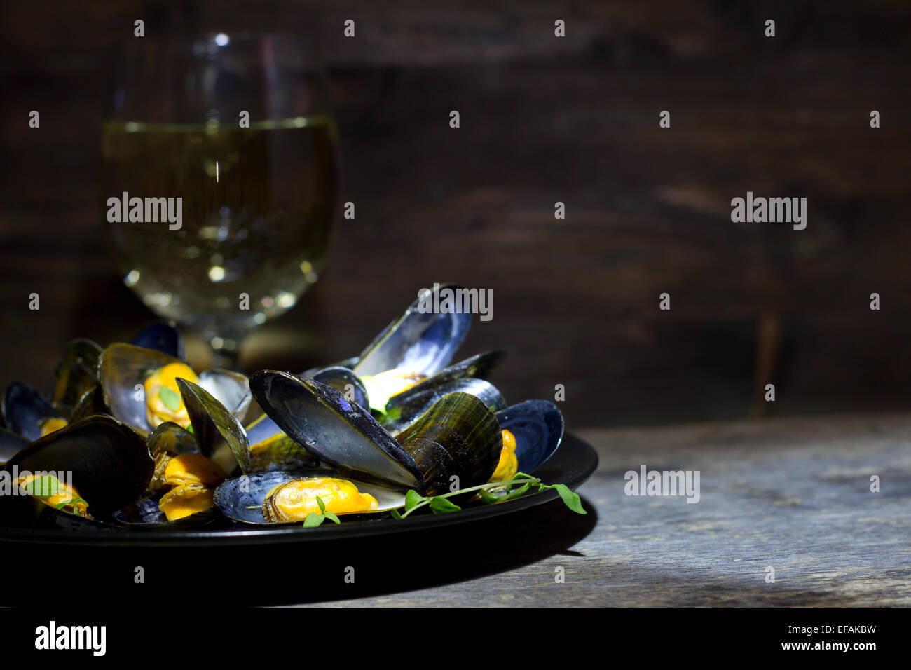 Mussels with glass of white wine and thyme in the dark - Stock Image
