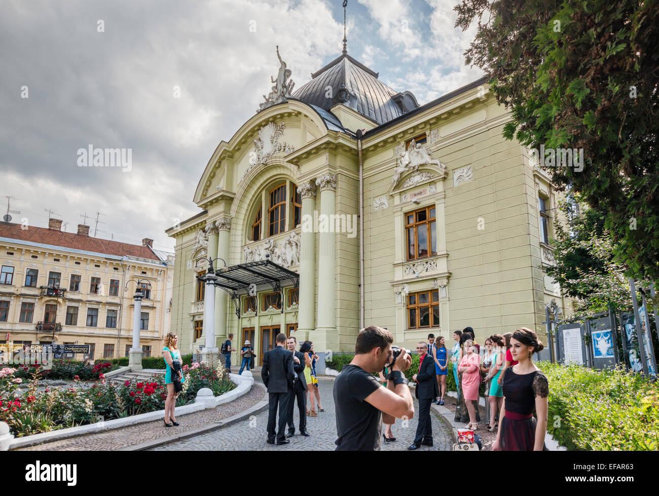 Young women and men at Olha Kobylianska Theatre of Music and Drama, 1905, Theatre Square in Chernivtsi, Bukovina - Stock Image