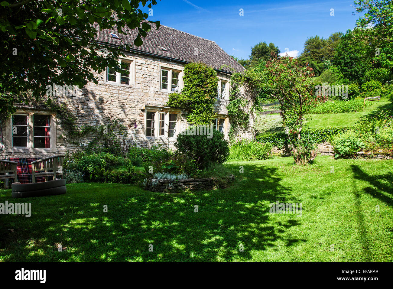 A pretty stone cottage in the Cotswold countryside. - Stock Image