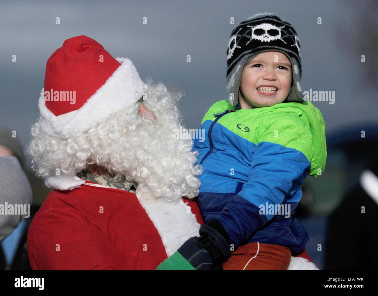 A Us Air Force Airman Dressed As Santa Claus Holds A Child From The