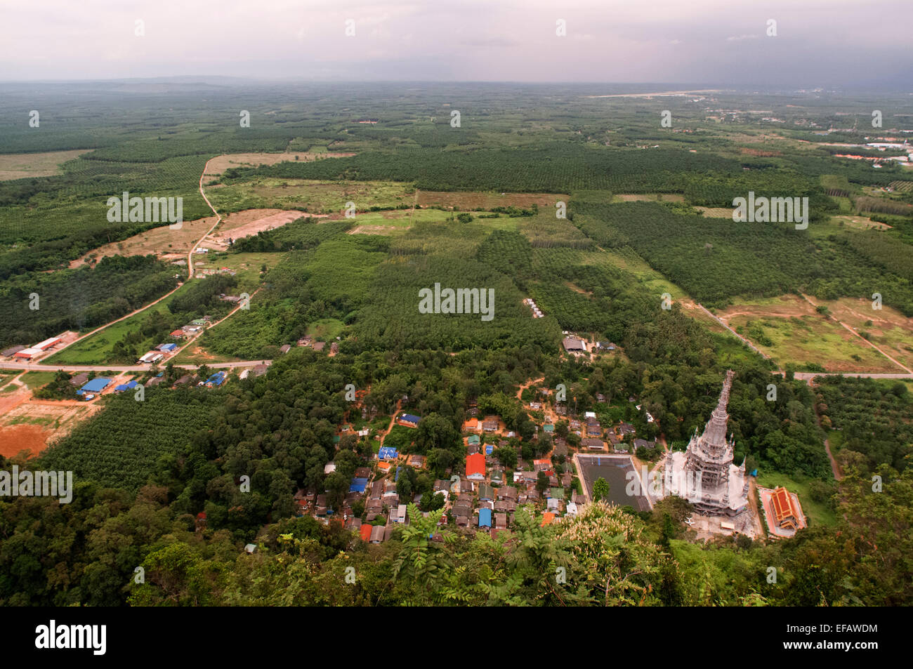 Looking down from Buddhist shrine and statue on top of the mountain towards Tiger Cave Temple (Wat Tham Sua), Krabi, - Stock Image
