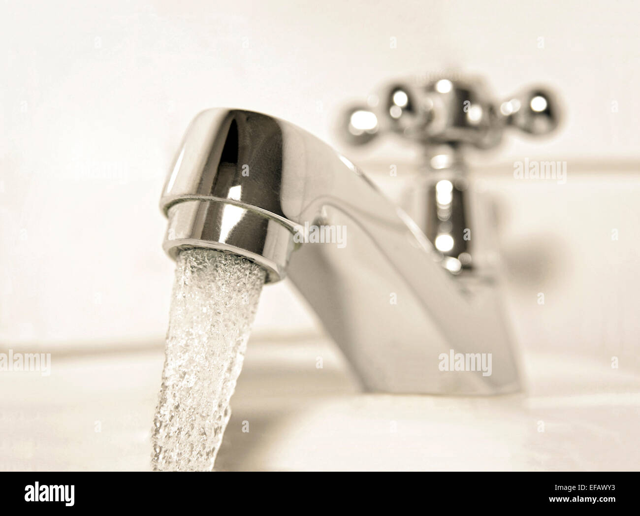 Faucet with running water in a bathroom Stock Photo