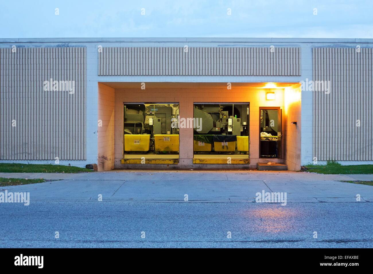 Open garage doors at an industrial laundromat loading dock - Stock Image