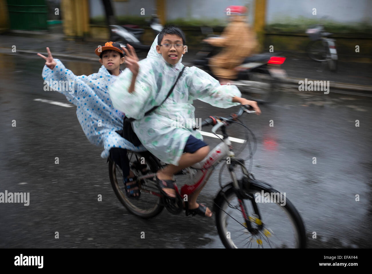 Schoolboys Cycling in the Rain in Hoi An Vietnam - Stock Image