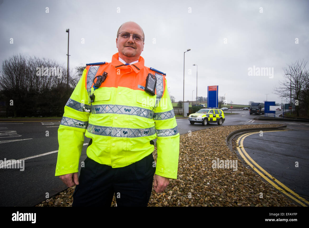 Traffic Officer at Watford Gap service station with traffic police car behind - Stock Image