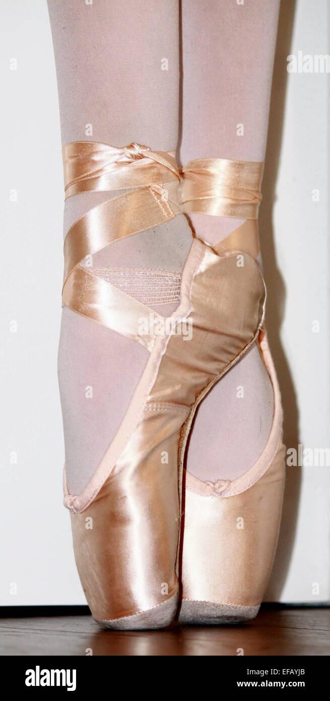 A close up of a ballet dancer's feet en pointe. - Stock Image