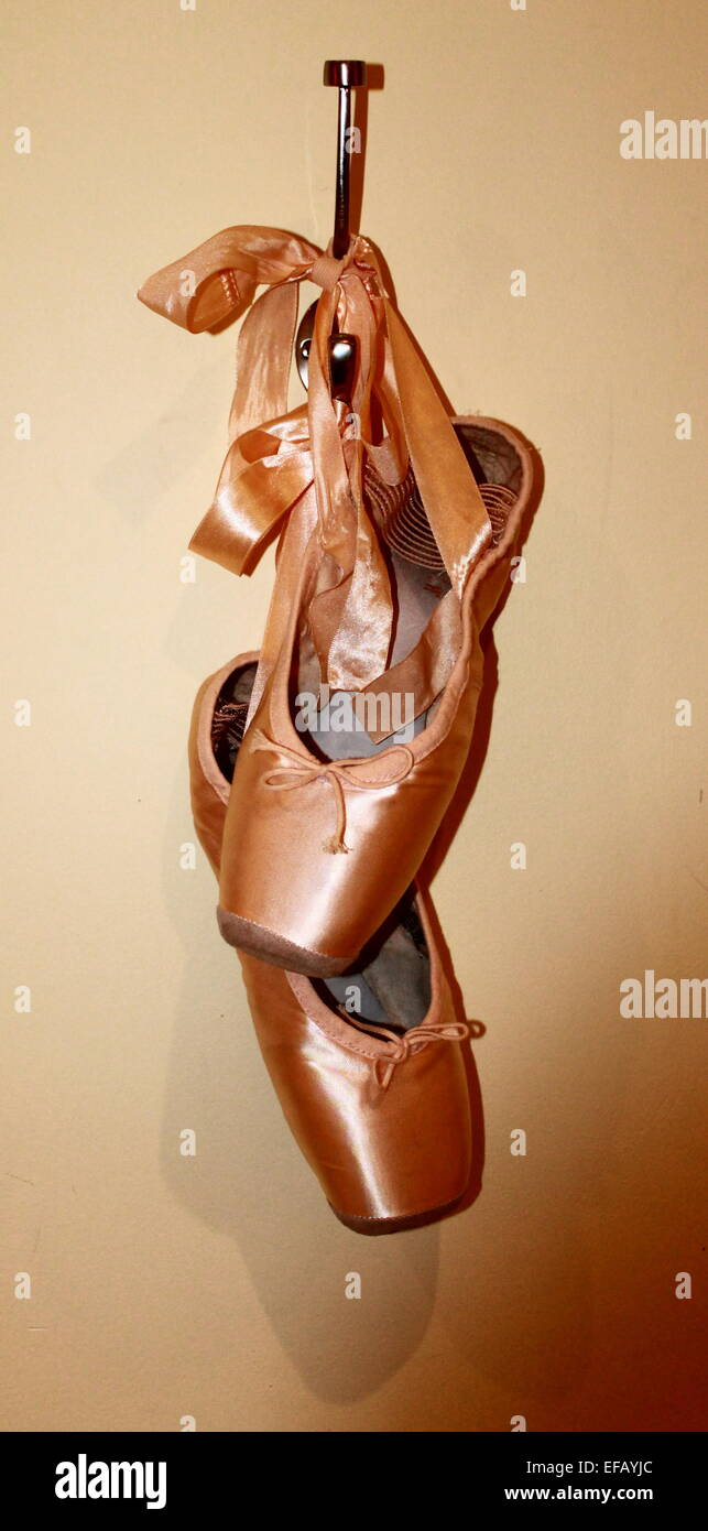 Pointe ballet shoes hanging on a hook. - Stock Image