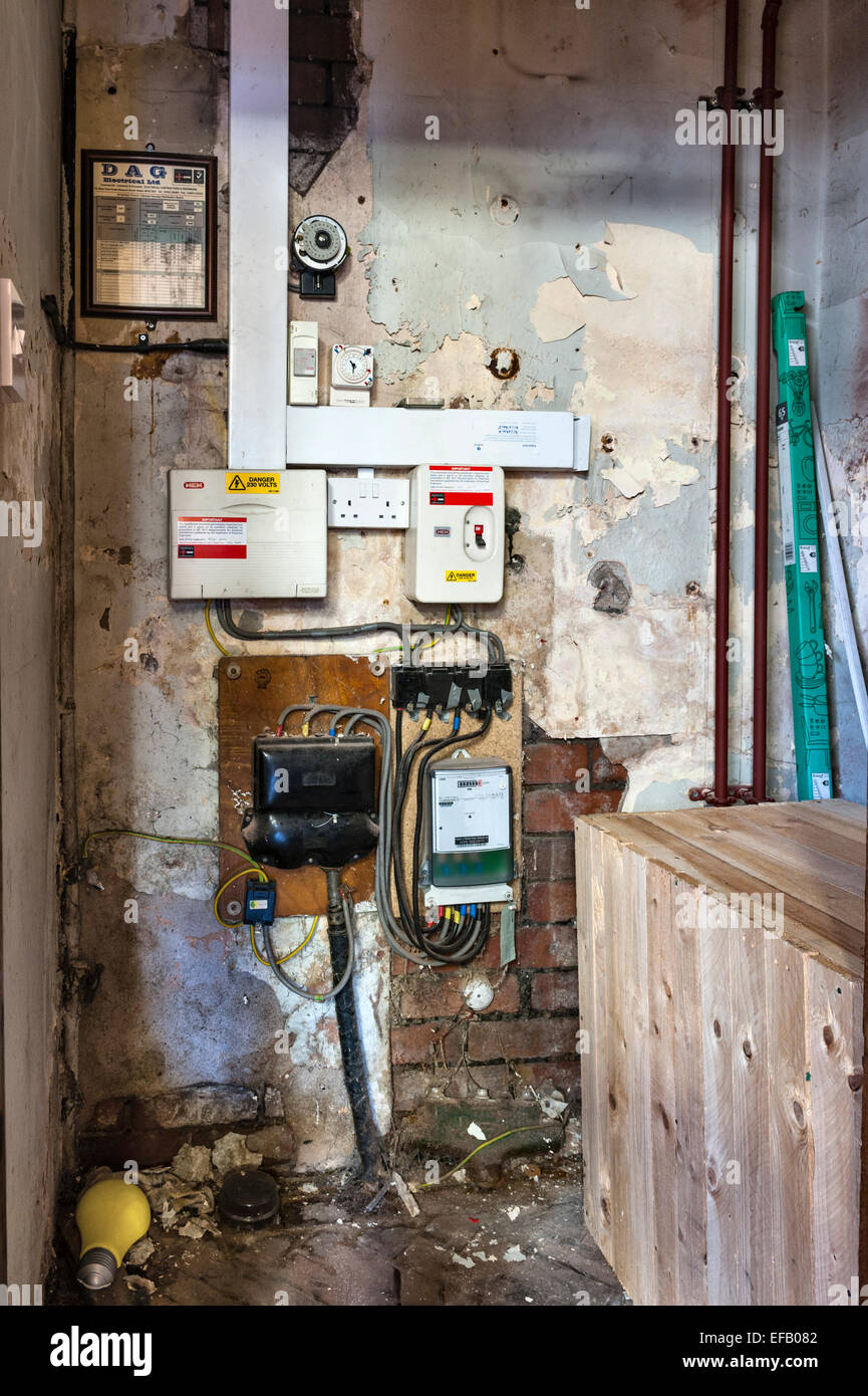 outdated electrical wiring and fuseboxes on a damp wall in an old building - Stock Image
