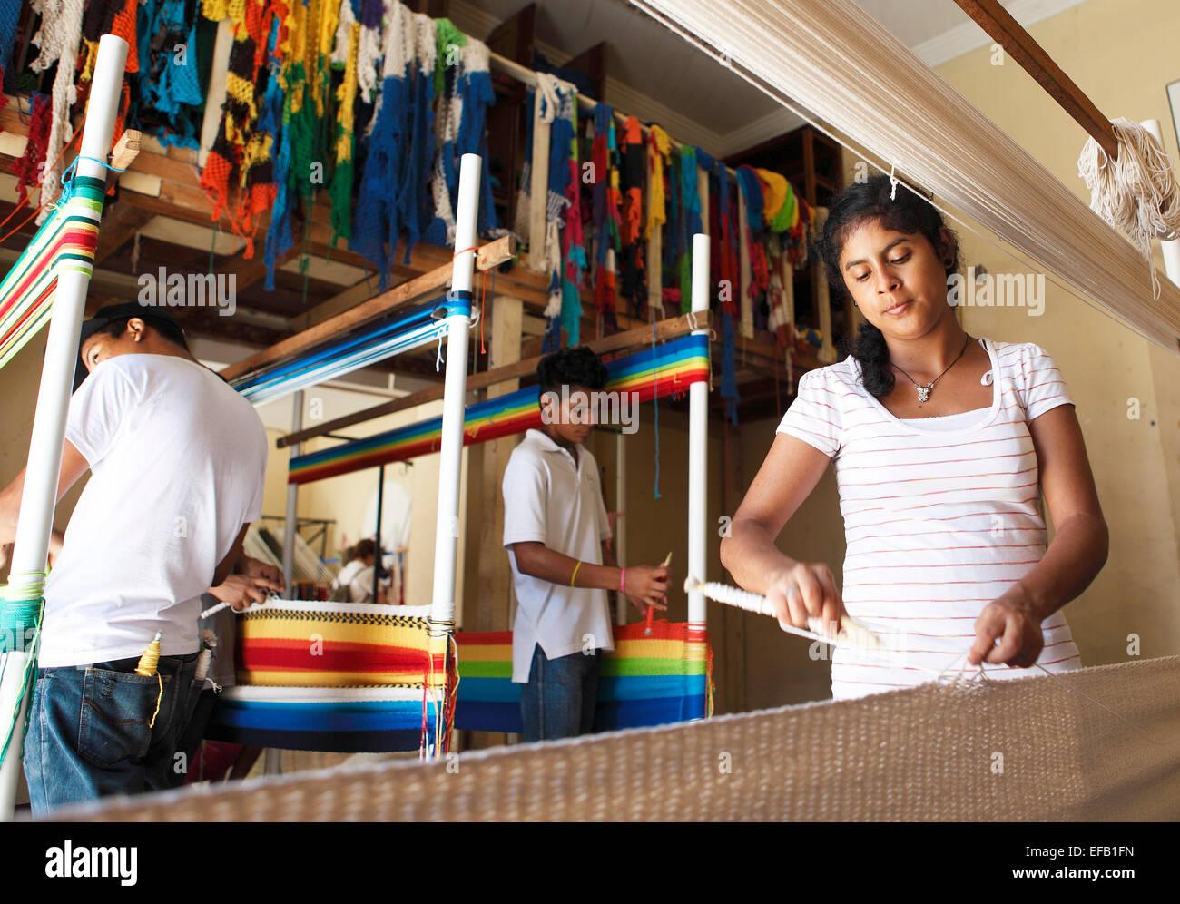 Woman and men weaving hammocks by hand, Granada, province of Granada, Nicaragua - Stock Image