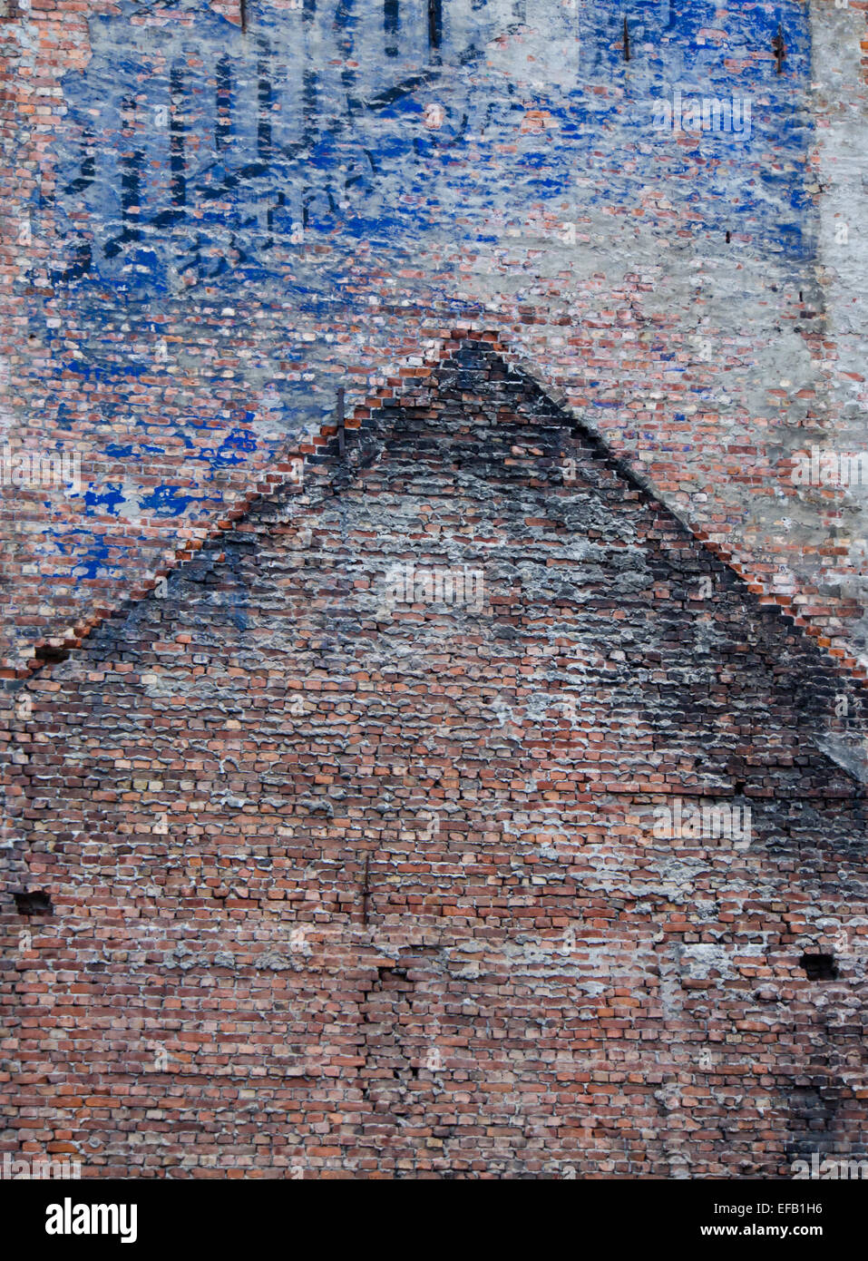 Red brick wall with imprint of former house gable and remains of old blue advertising, Oslo Norway - Stock Image