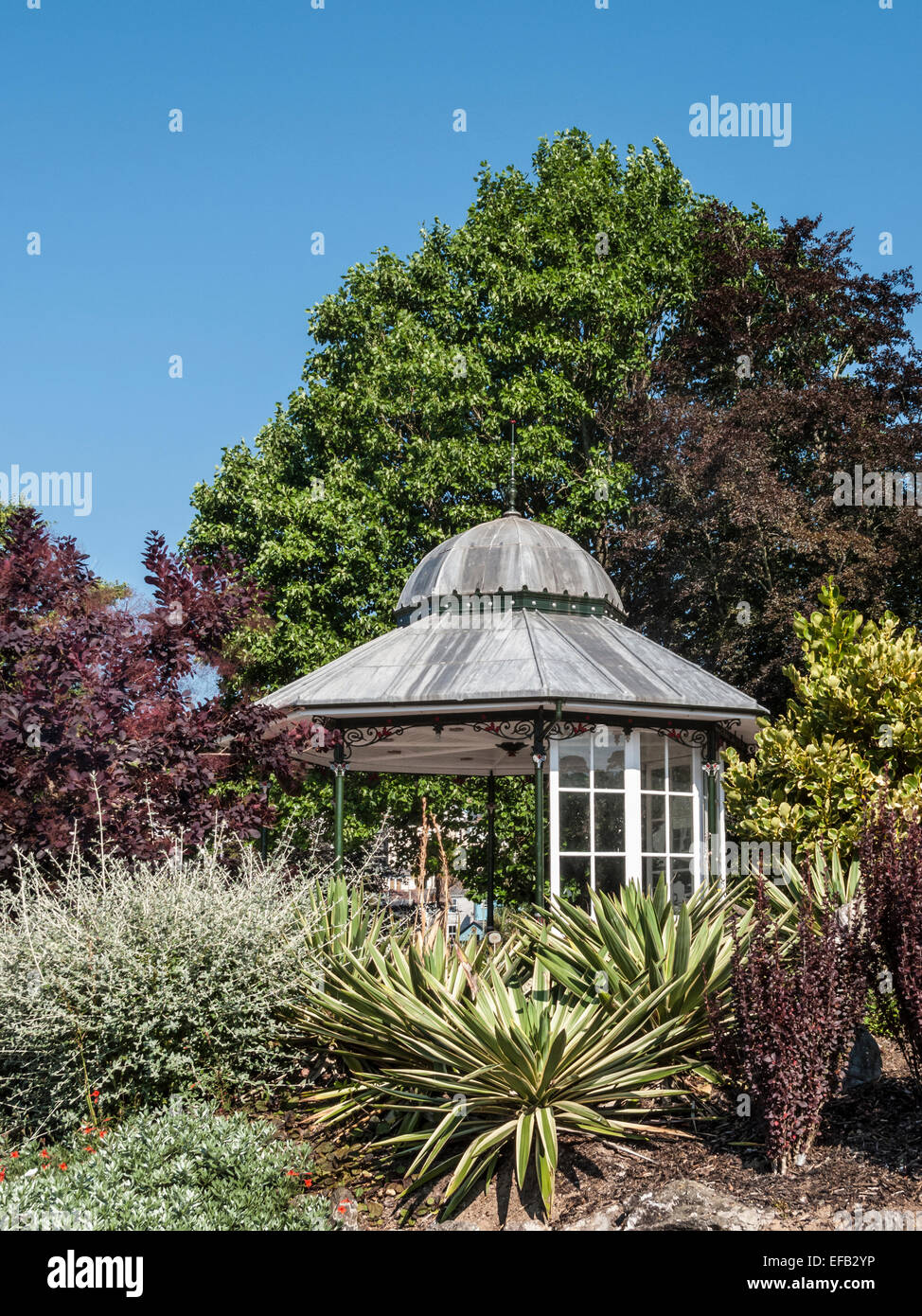 The town bandstand amongst exotic plants in Britannia Gardens, Dartmouth, South Devon - Stock Image
