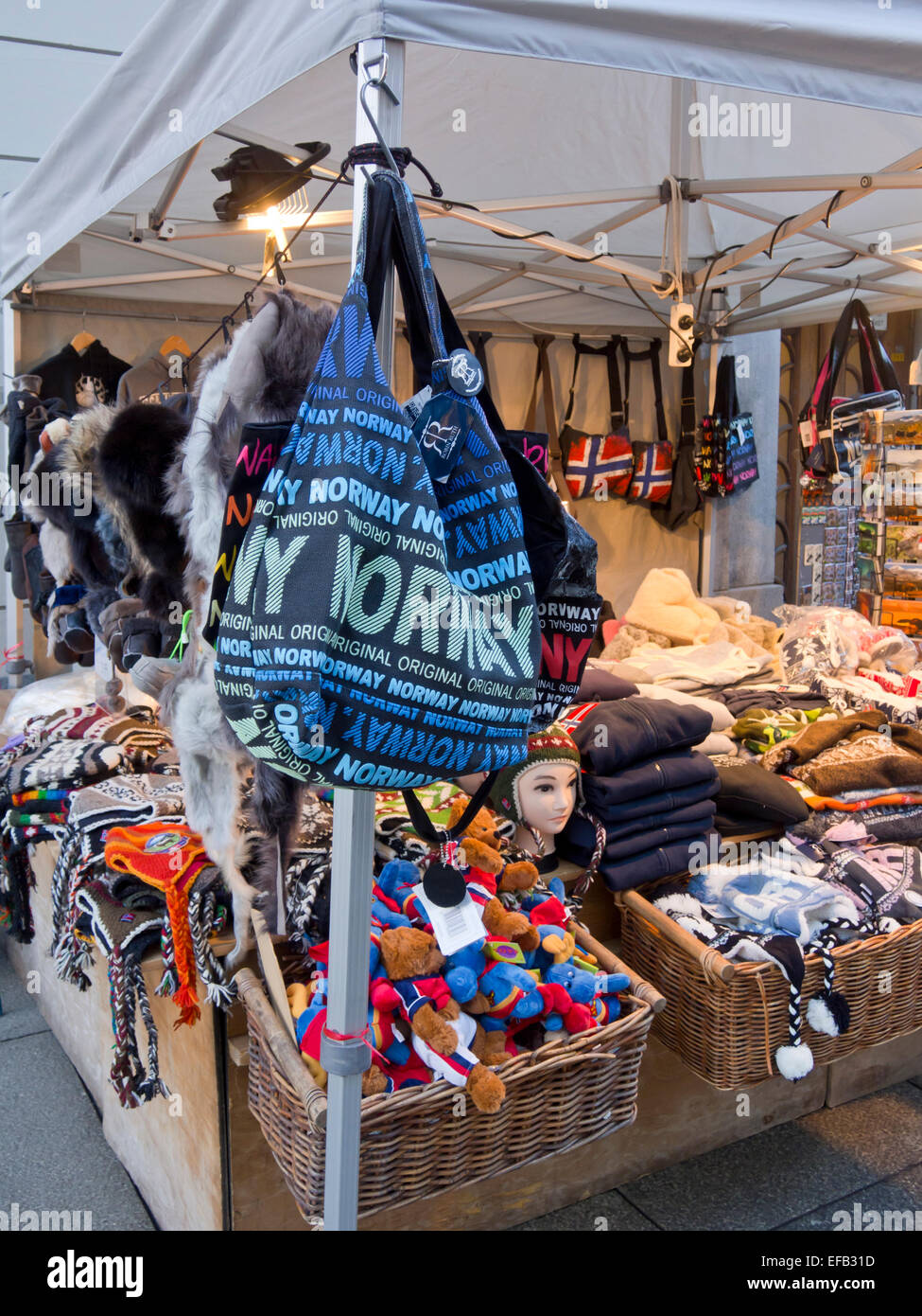 Blue touristy bag with Norway written in in many sizes, stall selling warm caps and souvenirs in Oslo - Stock Image