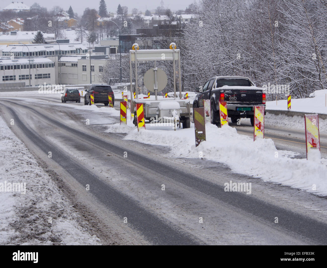 Winter roadworks, necessary but snow brings extra challenges for motorists and workers alike, Oslo Norway - Stock Image