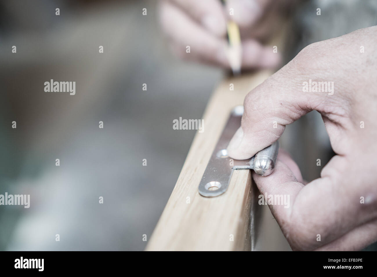 Closeup of carpenter hand with pencil working on door hinge - Stock Image