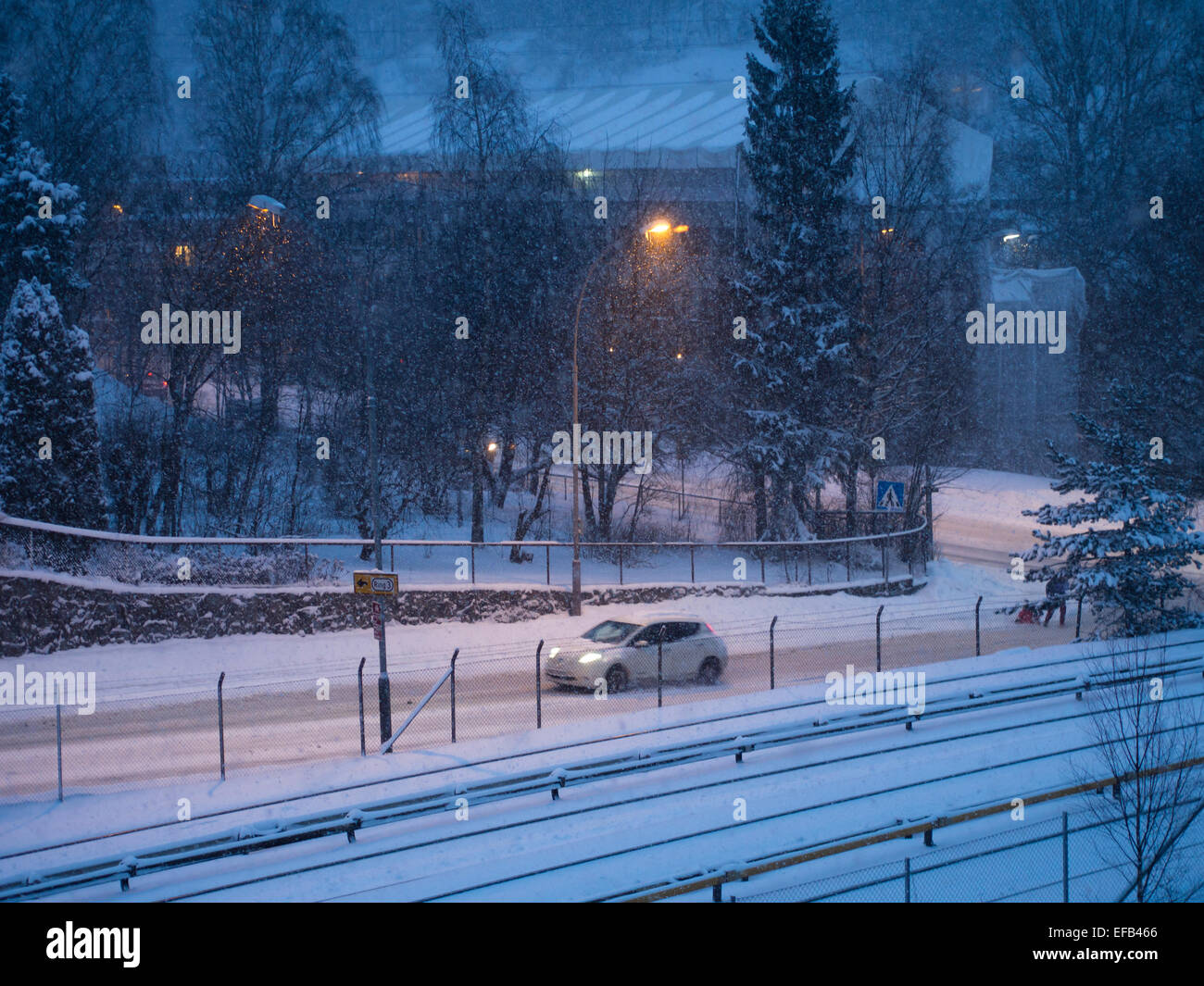 Blue hour, early winter morning in Brynseng Oslo Norway, snowing, road, traffic and streetlights - Stock Image