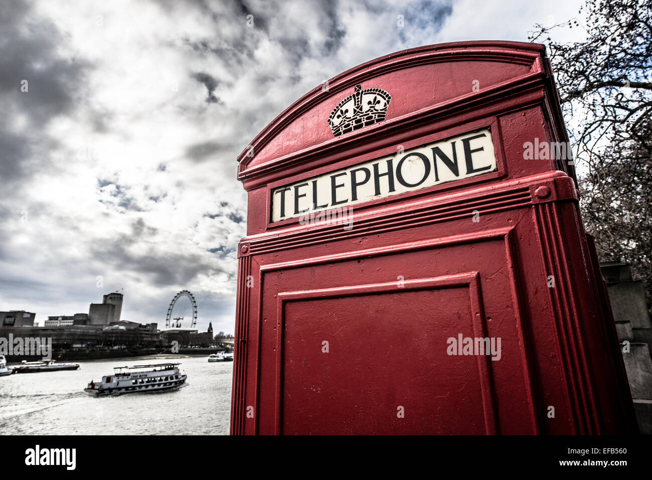 Red telephone box beside the River Thames - Stock Image