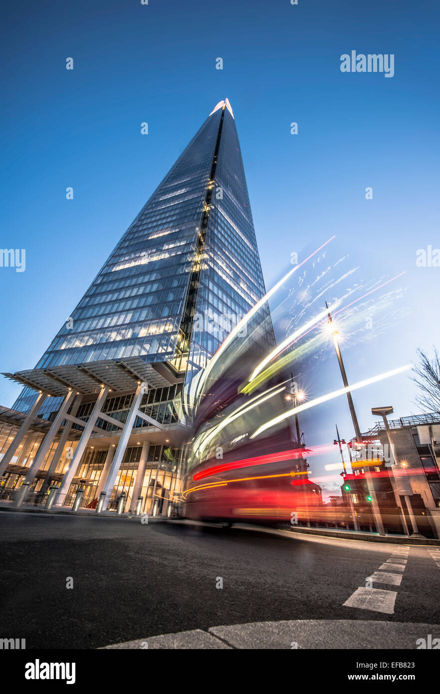 The Shard at dusk with bus moving past - Stock Image
