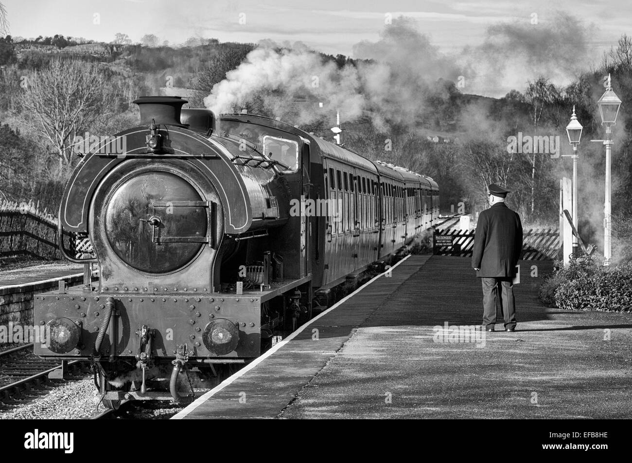 Black and white view of the station master waiting on the platform at Darley Dale railway station as a passenger Stock Photo