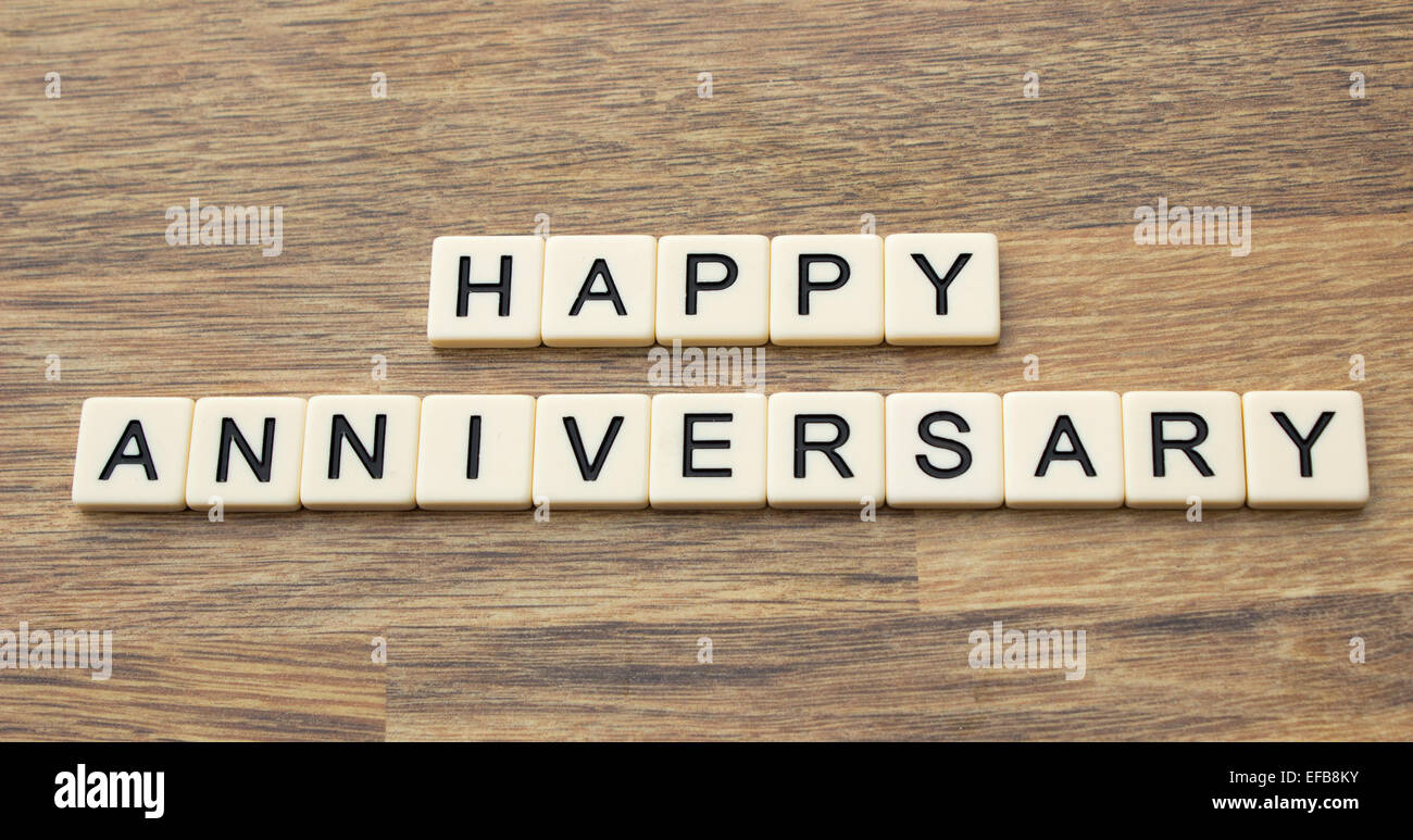 the word happy anniversary written in tiles on a wooden surface