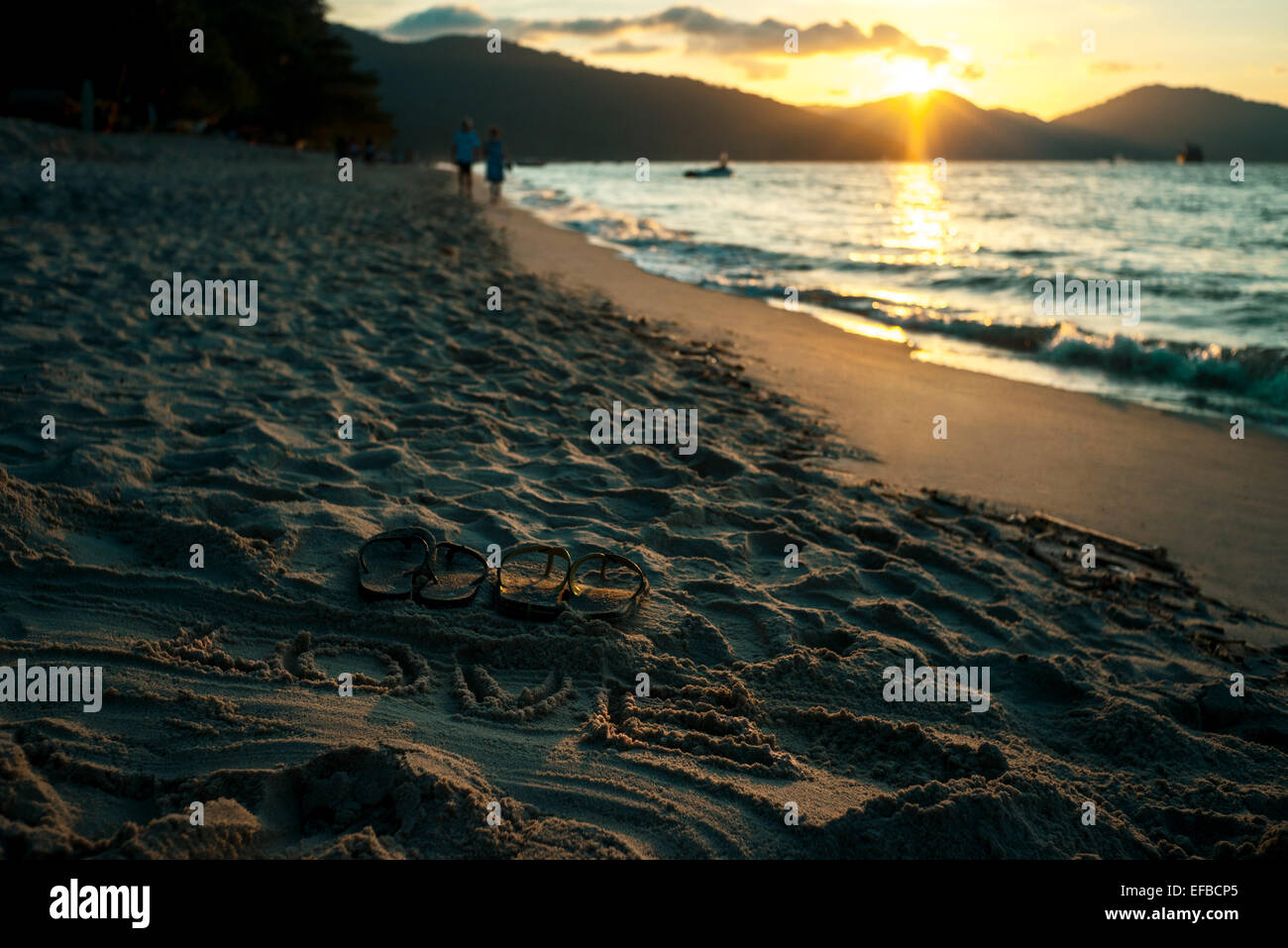 Sand writing of the word LOVE with sandals at seaside during sunset - Stock Image